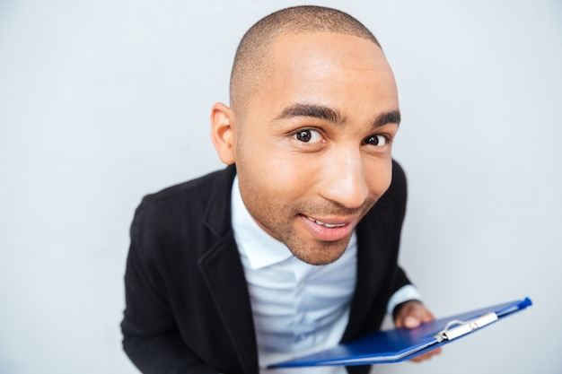 Closeup of smiling amusing african american young man holding clipboard