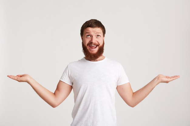 Closeup of smiling attractive young man hipster with beard wears t shirt feels happy and points to the side at copyspace with finger isolated over white wall