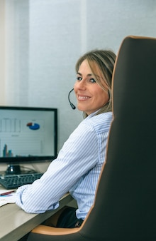 Closeup of smiling blonde secretary with headset looking while working with computer in office