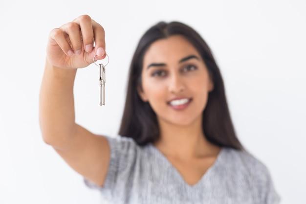 Closeup of smiling blurred woman raising keys