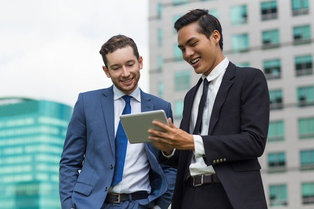 Closeup of smiling coworkers using tablet outdoors