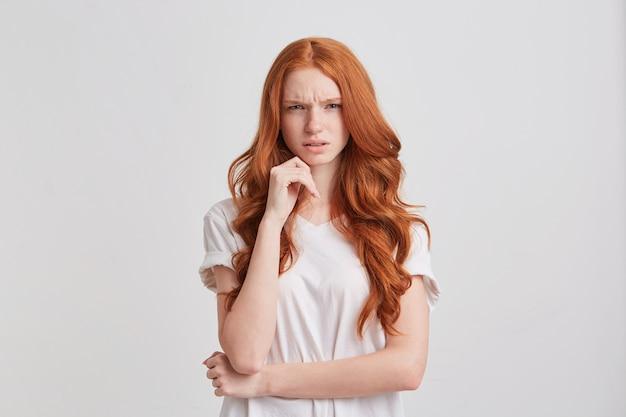 Primo piano della giovane donna sorridente adorabile della testarossa con capelli ondulati lunghi