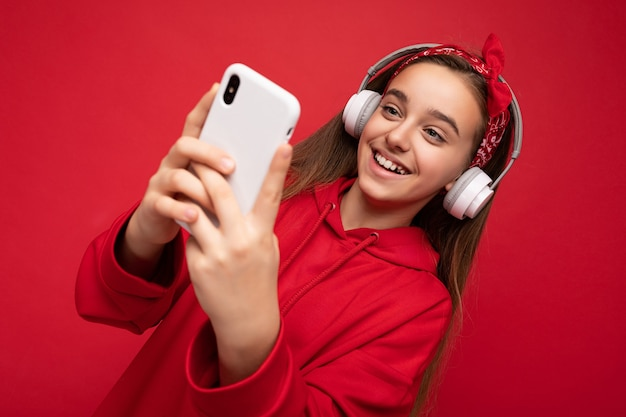 Closeup smiling positive attractive brunette girl wearing red hoodie isolated on red