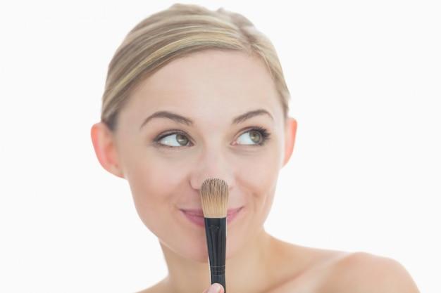 Closeup of smiling young woman with makeup brush