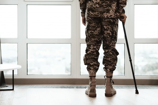 Closeup soldiers legs leaning on crutch by window.
