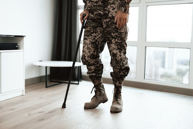 Closeup soldiers legs leaning on crutch near sofa