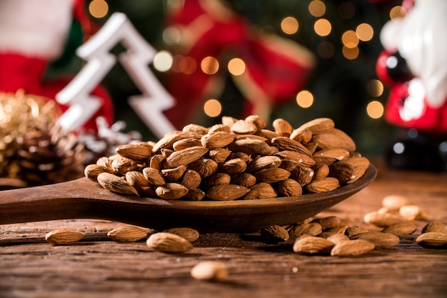 Closeup of some roasted almonds on rustic old wooden table with christmas background.