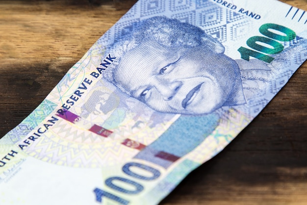 Closeup of a south african rand bill on a wooden surface