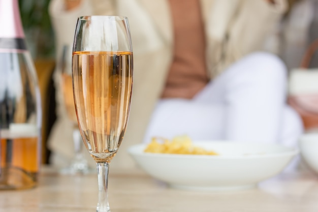 Closeup on sparkling rose wine glass with snacks bowl and woman on background friends meeting
