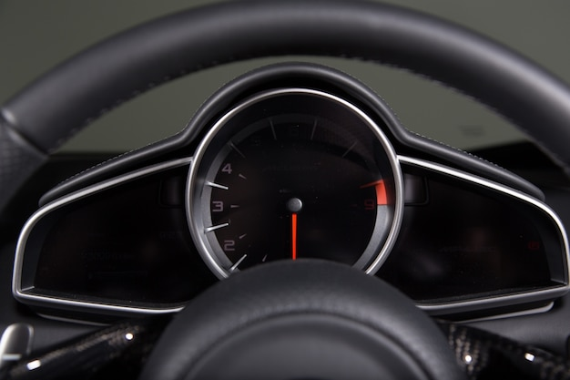 Closeup of a speedometer and a steering wheel of a modern car under the lights