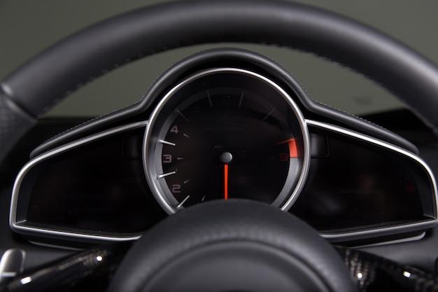 Primo piano di un tachimetro e un volante di un'auto moderna sotto le luci