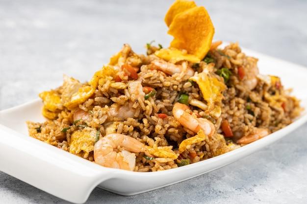 Primo piano di riso cotto piccante con carne, gamberi e verdure in un piatto