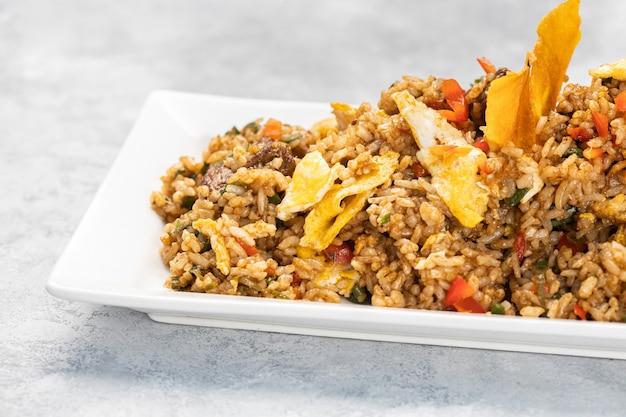 Primo piano di riso cotto piccante con carne, verdure e patatine in un piatto sul tavolo