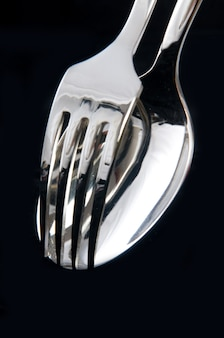 Closeup of spoon and fork on black background