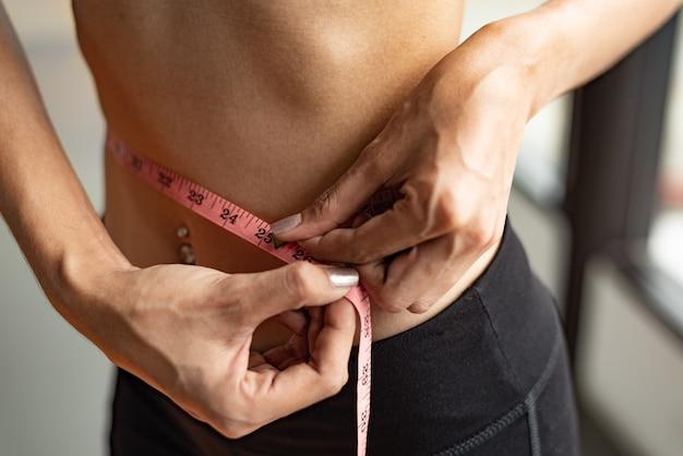 Closeup of sport happy slim woman using waist tape line in fitness gym sport club training