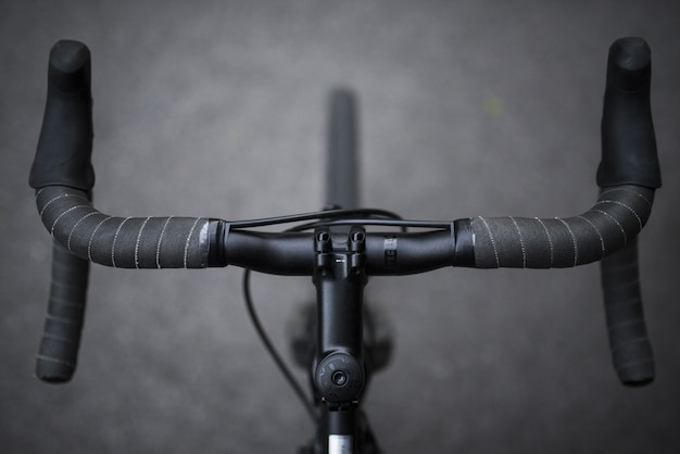 A closeup of a sports bicycle's front set handles shot in black and white