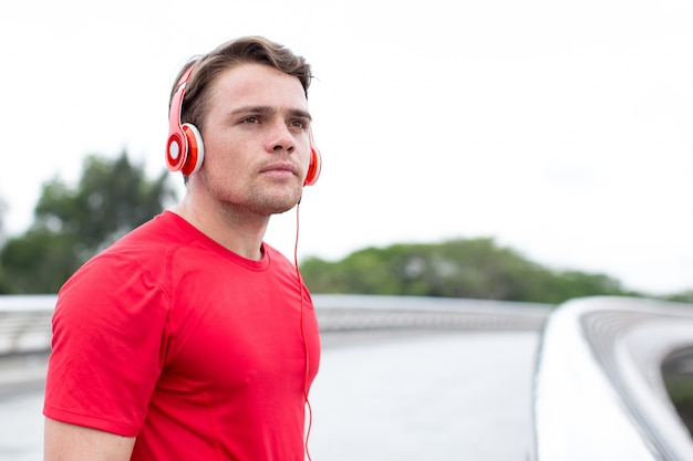 Closeup of sportsman listening to music outdoors