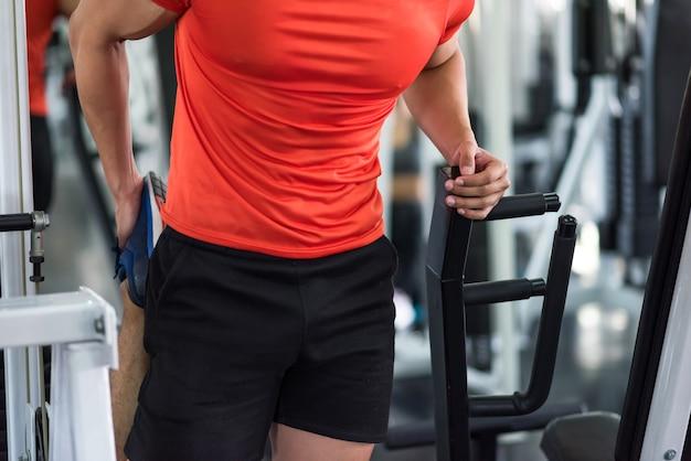 フィットネスジムでのトレーニングの前に足と脚を伸ばすクローズアップスポーティな筋肉の若い男