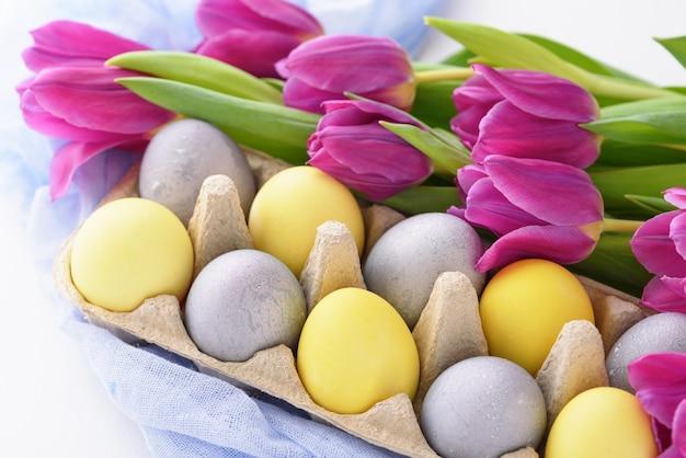 白い背景の上のpaschal卵と紫色のチューリップのクローズアップ春のお祝いイースター構成