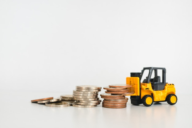 Closeup stack coins with folklift truck using as business and industrial concept
