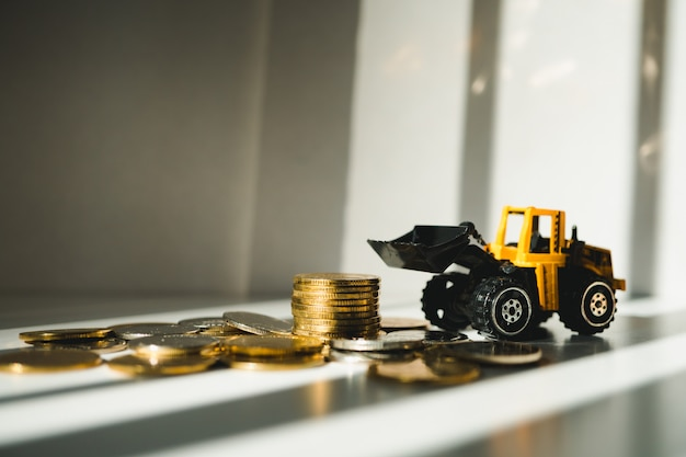 Closeup stack coins with yellow tractor using as business and industrial concept