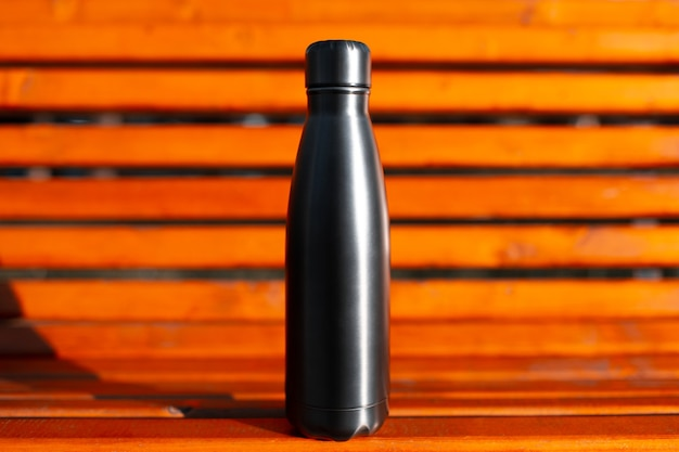 Closeup of stainless thermo water bottle of black on background of orange wooden bench. reusable bottles zero waste eco concept.