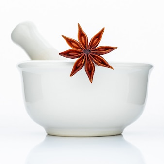 Closeup star anise in the white mortar isolated on white