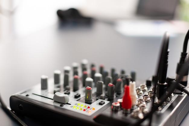 Primo piano della stazione per registrare e parlare durante il podcast online. influencer che crea contenuti sui social media con microfono di produzione in uno studio domestico professionale con attrezzature moderne