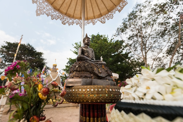 Closeup of statue of buddha with sand pagoda background at temple in songkran festival