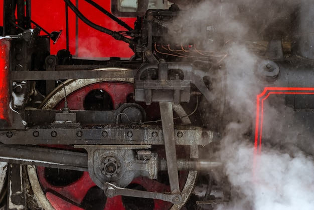 Closeup of a steam locomotive wheel with valve gear and connecting rods