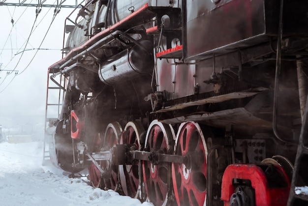 Closeup of a steam locomotive wheels with valve gear and connecting rods
