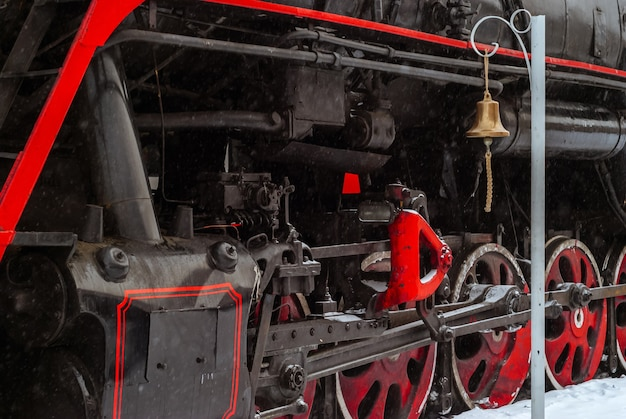 Closeup of a steam locomotive wheels with valve gear and station bell