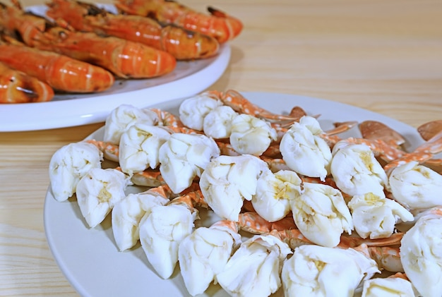 Closeup steamed flower crab legs with blurry flame grilled river prawns served on wooden table