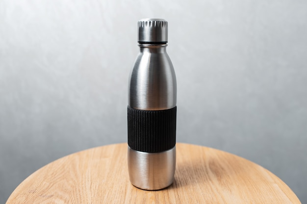 Closeup of steel reusable thermo water bottle on wooden table against background of textured grey wall. zero waste. no plastic.