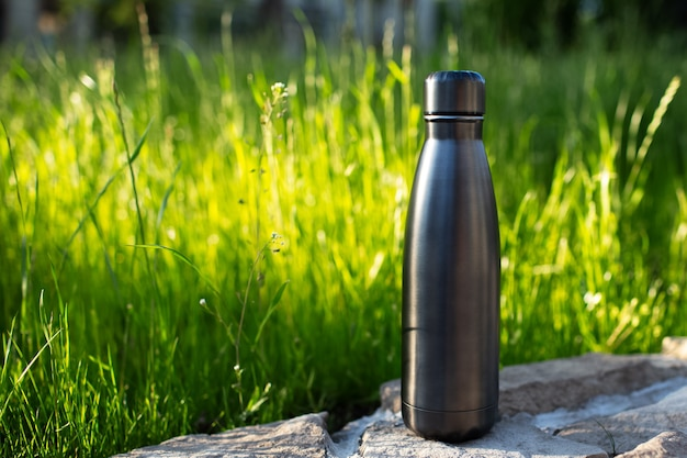 Closeup of steel thermo water bottle of black on background of green grass with copy space. reusable bottles zero waste eco concept plastic free.