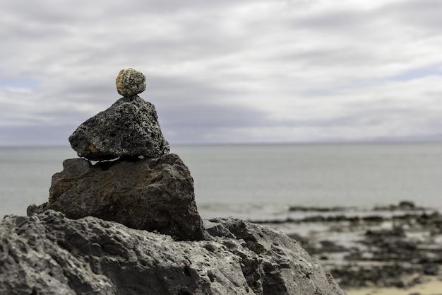 Primo piano delle pietre in cima a vicenda con il mare a lanzarote in spagna