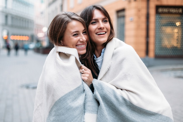 Closeup street stylish portrait of two girls friends posing together smiling and having fun