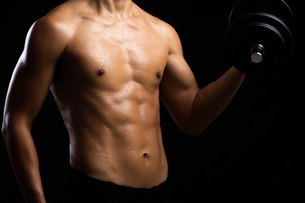 Closeup of a strength fitness body with dumbbell. fit young man