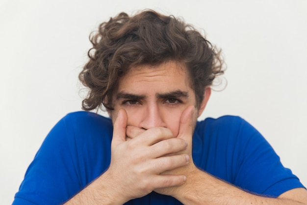 Closeup of stressed guy covering mouth