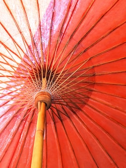 Closeup the structure of the red beach umbrella old made of wooden for protected sunlight.