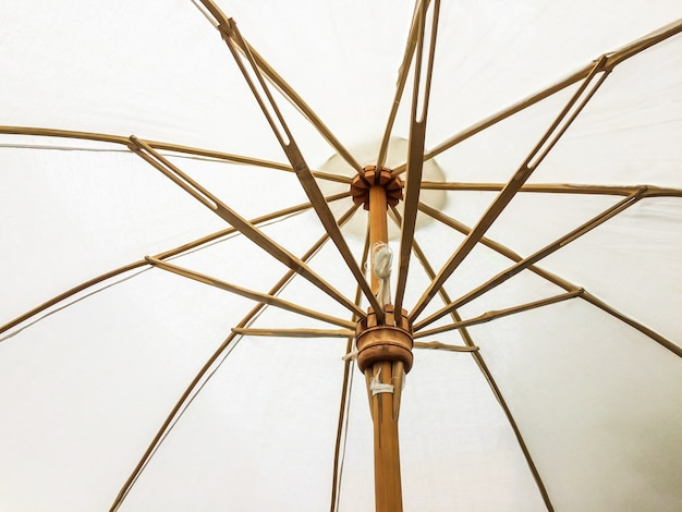 Closeup the structure of the white beach umbrella made of wooden for protected sunlight.