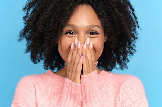 Closeup studio portrait of happy african girl. laughing dark skinned millennial woman looking at camera. cute positive mixed race female smiling covering her mouth and lips with hands, blue background
