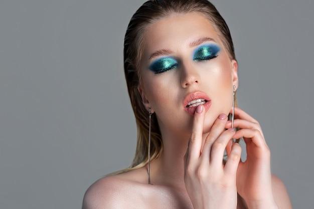 Студийный портрет крупным планом модной блондинки с влажными волосами и темно-синим дымчатым макияжем глаз. модель позирует с обнаженными плечами на сером фоне. пустое пространство