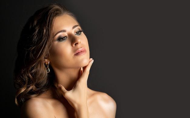影と裸の肩でポーズをとってプロのメイクアップでファッショナブルなブルネットの女性のクローズアップスタジオの肖像画。テキスト用のスペース