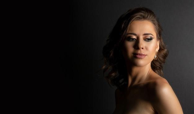 影と裸の肩でポーズをとってプロのメイクアップで輝かしいブルネットの女性のクローズアップスタジオの肖像画。テキスト用のスペース