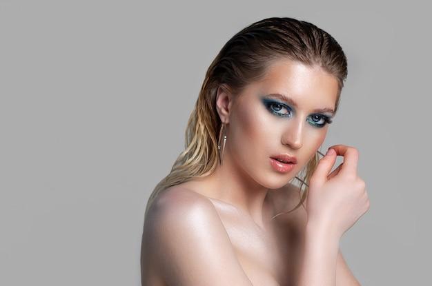 濡れた髪と深い青色のスモーキーアイメイクで魅惑的なブロンドの女性のクローズアップスタジオの肖像画。灰色の背景の上に裸の肩でポーズをとるモデル。空きスペース