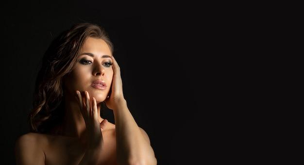 影と裸の肩でポーズをとってプロのメイクアップで見事なブルネットの女性のクローズアップスタジオの肖像画。テキスト用のスペース