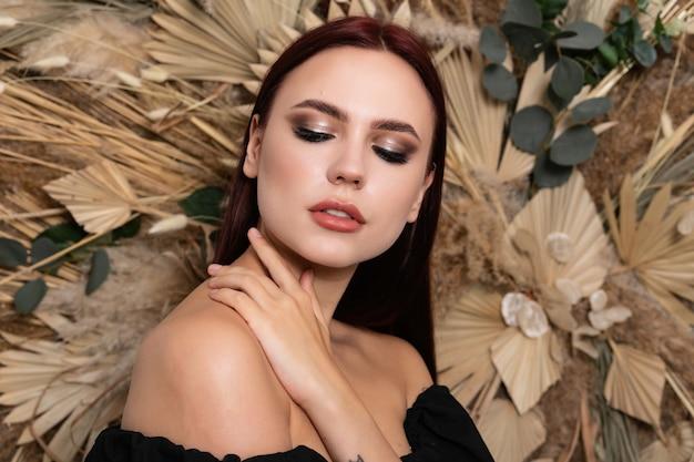 봄 마른 필드 꽃의 배경에 부르고뉴 입술을 가진 아름 다운 갈색 머리 여자 여자의 근접 촬영 스튜디오 초상화. 열린 어깨