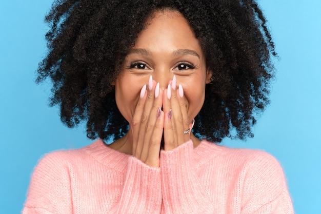 행복 한 아프리카 여자의 근접 촬영 스튜디오 초상화입니다. 카메라를보고 어두운 피부 밀레 니얼 여자를 웃 고있다. 손, 파란색 배경으로 그녀의 입과 입술을 덮고 웃는 귀여운 긍정적 인 혼혈 여성
