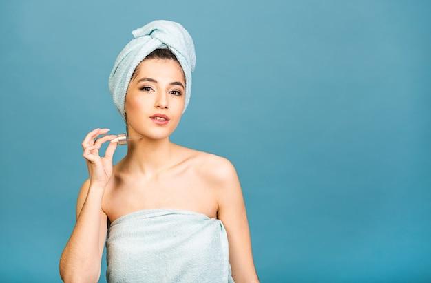 Студийный портрет крупным планом с молодой женщиной в банном полотенце на голове, изолированной на копировальном пространстве, применяя масляную сыворотку из пипетки.